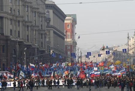 People walk with flags and posters as they attend a demonstration on National Unity Day in Moscow