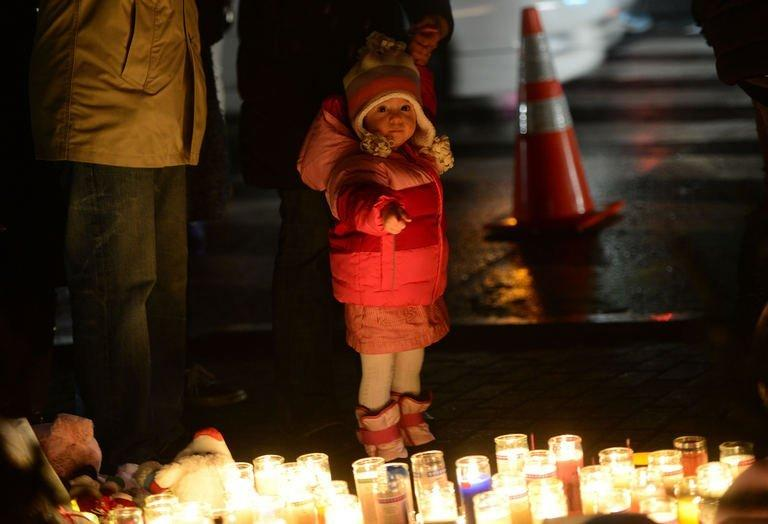 A young child points at candles as people pay their respects at a makeshift shrine to the victims of the Newtown school shooting, Connecticut, December 16, 2012. President Barack Obama has vowed to battle gun violence, casting the fight as a nation's duty to protect its young, as the Connecticut town of Newtown prepared to bury the first two victims of last week's rampage at an elementary school