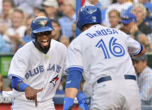 Toronto Blue Jays shortstop Jose Reyes, left, celebrates teammate Mark DeRosa, right, after scoring against the Detroit Tigers during the first inning of a baseball game in Toronto on Tuesday, July 2, 2013. (AP Photo/The Canadian Press, Nathan Denette)