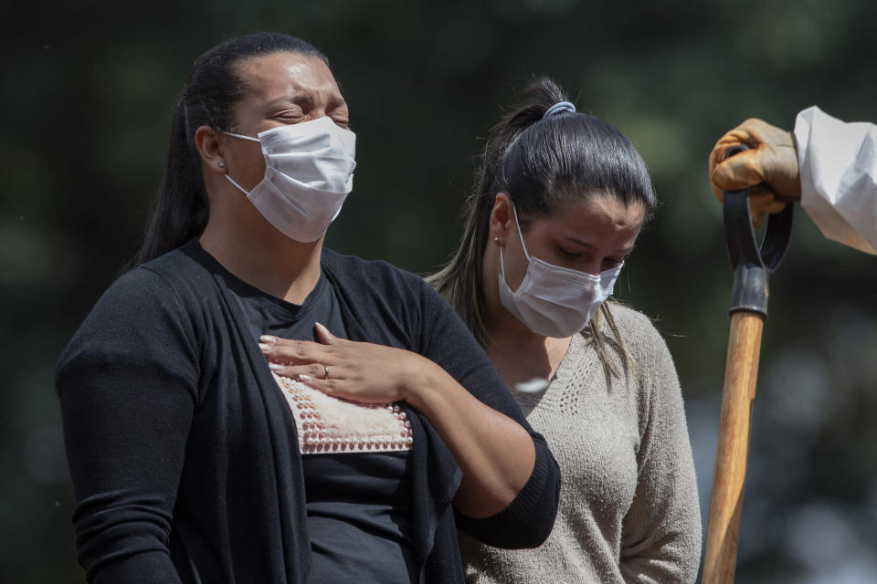People grieve during the burial of a relative who died from complications related to COVID-19 at the Vila Formosa cemetery in Sao Paulo, Brazil, Wednesday, April 7, 2021. (AP Photo/Andre Penner)