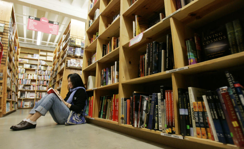 FILE - A woman reads a book in Powell's Bookstore in downtown Portland, Ore., on, Jan. 4, 2008. On Thursday, the American Booksellers Association said that membership increased from 1,635 to 1,701 since May 2020, the additions a combination of brand new stores and existing stores that had not previously been part of the independents' trade group. While association CEO Allison Hill and others had feared that hundreds of stores could go out of business during the 2020-21 holiday season, the ABA so far has only tallied 14 closings in 2021, along with more than 70 last year. (AP Photo/Don Ryan, File)