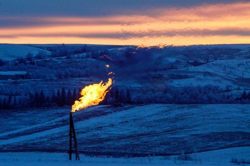 A natural gas flare on an oil well pad burns as the sun sets outside Watford City, North Dakota