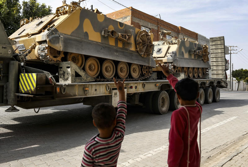 Children wave to a Turkish forces truck transporting armoured personnel carriers at the border with Syria in Karkamis, Gaziantep province, southeastern Turkey, Tuesday, Oct. 15, 2019. Turkey defied growing condemnation from its NATO allies to press ahead with its invasion of northern Syria on Tuesday, shelling suspected Kurdish positions near the border amid reports that Syrian Kurds had retaken a key town. (AP Photo/Emrah Gurel)