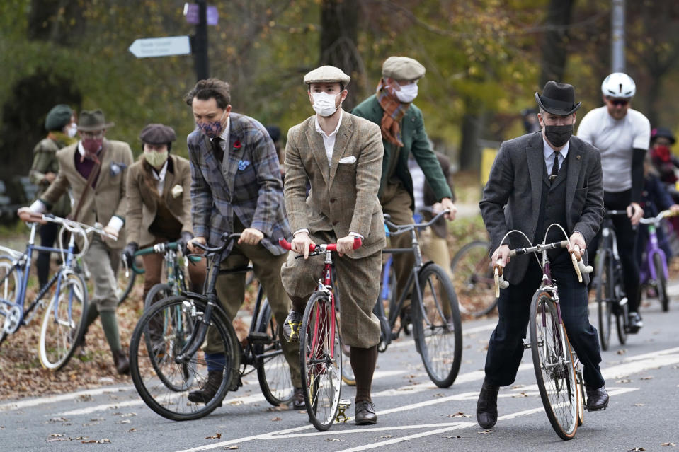 Participants in the 2020 Brooklyn Tweed Ride mount their bikes as they ride a loop in Prospect Park after a stop to sip champagne and tea at a colonnaded Grecian shelter, Sunday, Nov. 15, 2020, in the Brooklyn borough of New York. (AP Photo/Kathy Willens)
