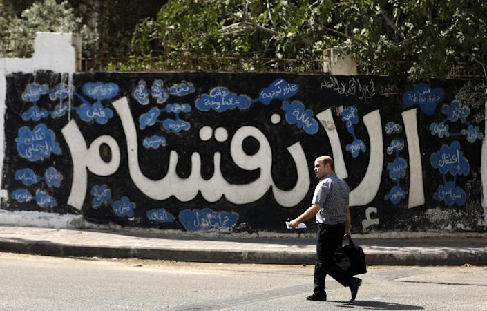 """A Palestinian man walks past graffiti in Gaza City that reads """"Division"""" on September 17, 2017, after Hamas announced it had agreed to steps toward resolving a decade-long split with the Fatah movement and was ready to hold elections (AFP Photo/MAHMUD HAMS)"""