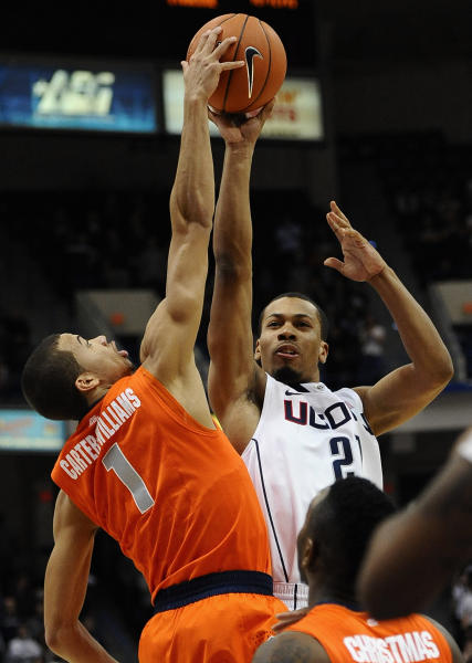 Syracuse's Michael Carter-Williams, left, blocks a shot-attempt by Connecticut's Omar Calhoun, right, during the second half of an NCAA college basketball game in Hartford, Conn., Wednesday, Feb. 13, 2013. Connecticut won 66-58. (AP Photo/Jessica Hill)