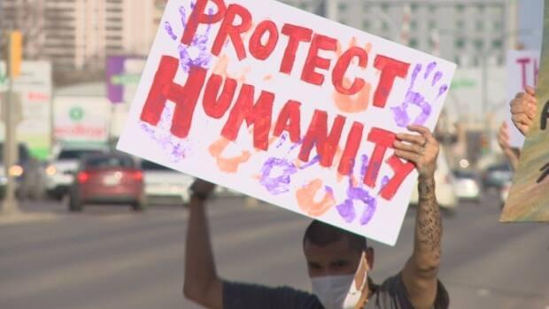 A person holds a sign reading 'protect humanity' as they rally in support of Prairie Harm Reduction in Saskatoonon April 7, 2021. (Matt Garand/CBC - image credit)