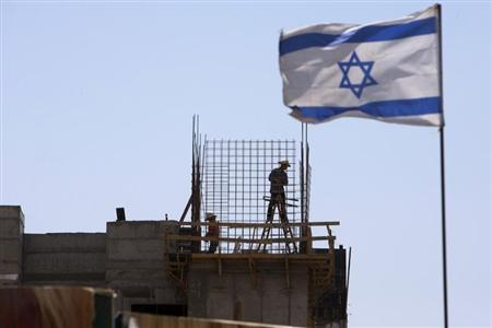 An Israeli flag is seen as labourers work on a construction site in a Jewish settlement near Jerusalem known to Israelis as Har Homa and to Palestinians as Jabal Abu Ghneim May 7, 2013. REUTERS/Ronen Zvulun/Files