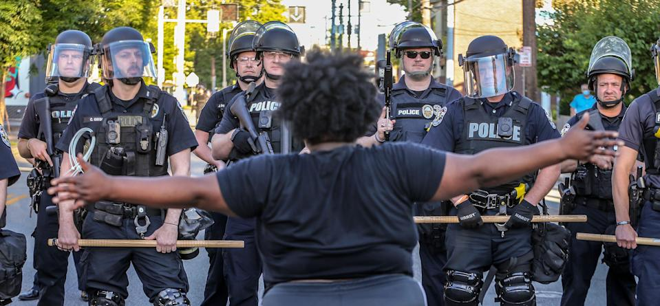 Police in riot gear block a crowd protesting the killing of Breonna Taylor from moving down a road in Louisville, Ky., on May 30, 2020.