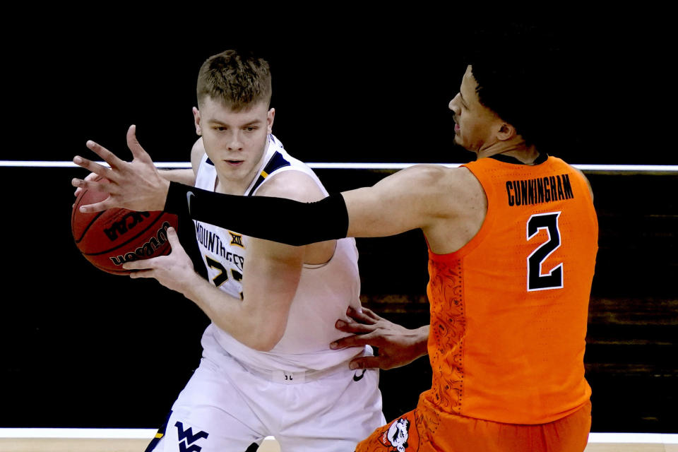 West Virginia's Sean McNeil is pressured by Oklahoma State's Cade Cunningham (2) during the first half of an NCAA college basketball game in the second round of the Big 12 Conference tournament in Kansas City, Mo., Thursday, March 11, 2021. (AP Photo/Charlie Riedel)