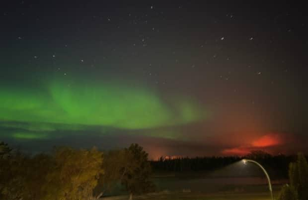 Light from the fire was visible Monday night along with the northern lights.