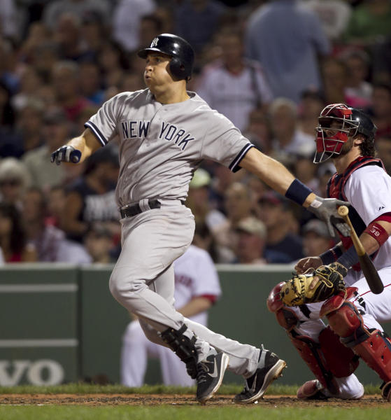 New York Yankees' Mark Teixeira watches the flight of his single off a pitch by Boston Red Sox's Jon Lester as Red Sox's Jarrod Saltalamacchia, right, looks on in the fifth inning of a baseball game at Fenway Park in Boston, Sunday, July 8, 2012. (AP Photo/Steven Senne)