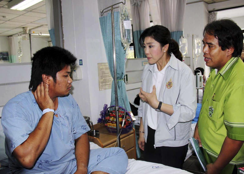 Thailand's Prime Minister Yingluck Shinawatra, center, talks with an injured worker, left, at a hospital following a factory fire in Rayong province, Thailand Sunday, May 6, 2012. A fire caused by explosions in one of the world's largest petrochemical industrial estates have killed 12 and injured more than 100 people in eastern Thailand. (AP Photo)