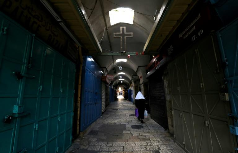 A woman walks past closed shops along a deserted alley in the Old City of Jerusalem (AFP Photo/Emmanuel DUNAND)