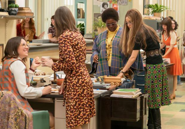 Gloria Steinem in a vintage Yves Saint Laurent skirt (far right, Rose Byrne) speaks with Margaret Sloan (second from right, Bria Henderson) in the 'Ms. Magazine' offices.