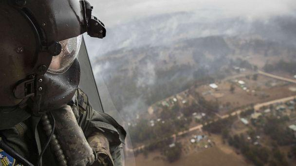 PHOTO: ELeading seaman aircrew Brendan Menz looks out of a helicopter over Southern New South Wales, Australia, Jan. 6 2020, as scattered showers fall in areas where bush fire burn. (Australian Dept. of Defense via EPA/Shutterstock)