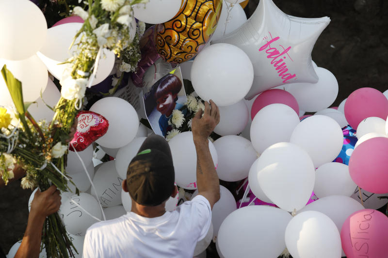 Family members place balloons and flower arrangements on the grave of 7-year-old murder victim Fatima in Mexico City, Tuesday, Feb. 18, 2020. Fatima's body was found wrapped in a bag and abandoned in a rural area on Saturday. Five people have been questioned in the case, and video footage of her abduction exists. (AP Photo/Marco Ugarte)