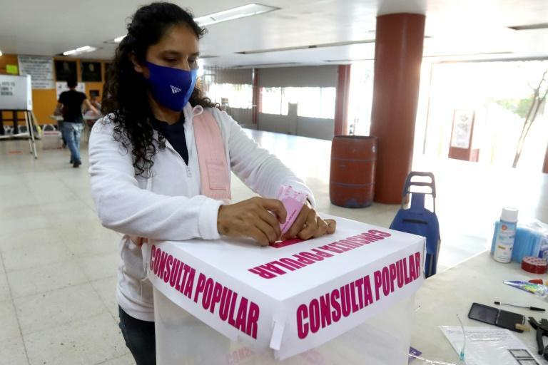 A woman casts her vote during a national referendum on whether to investigate past leaders for corruption, in Guadalajara, Jalisco state, Mexico, on August 1, 2021