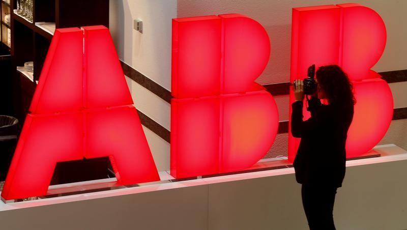 A woman takes pictures of the logo of Swiss power technology and automation group ABB in Zurich