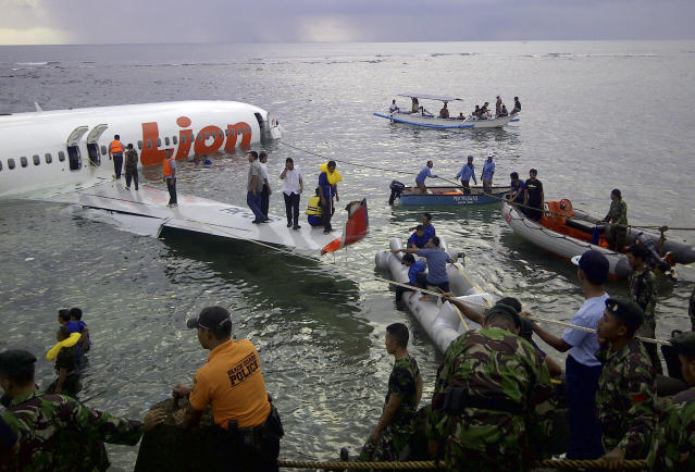 This photo released by Indonesia's National Rescue Team shows rescuers at the crash site of a Lion Air plane in Bali, Indonesia on Saturday, April 13, 2013. The plane carrying more than 100 passengers and crew overshot a runway on the Indonesian resort island of Bali on Saturday and crashed into the sea, injuring nearly two dozen people, officials said. (AP Photo/National Rescue Team)