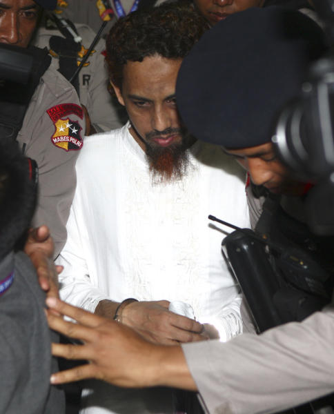 Indonesian militant Umar Patek, center, is escorted by police officers as he leaves the courthouse after being sentenced to 20 years in prison at West Jakarta district court in Jakarta, Indonesia, Thursday, June 21, 2012. Patek was convicted guilty of his role in the 2002 Bali bombings that killed 202 people. (AP Photo/Tatan Syuflana)
