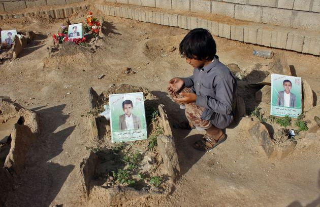 A Yemeni child at the graves of schoolboys who were killed in an August 2018 airstrike by a military coalition that included the UAE. (Photo: STRINGER via Getty Images)