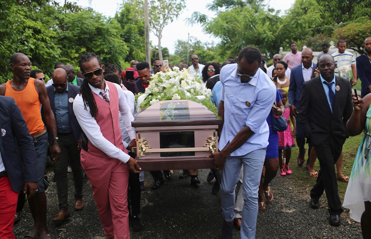 Jamaica's Olympic champion Usain Bolt (R) carries the coffin of high jump star Germaine Mason, who died on April 20 in a motorbike crash on the outskirts of Kingston, to the cemetery in Grange Hill, Portland, Jamaica May 21, 2017. REUTERS/Gilbert Bellamy