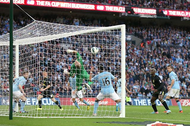 Wigan Athletic's Ben Watson (obscured) scores the winning goal past a helpless Manchester City goalkeeper Joe Hart