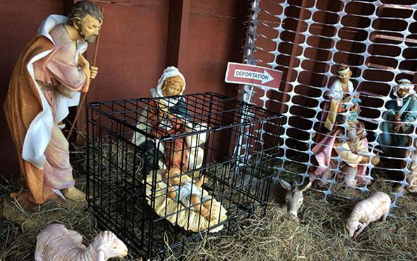"""The Nativity scene features baby Jesus in a cage and a fence labeled """"Deportation."""" (Photo: Saint Susanna Parish)"""