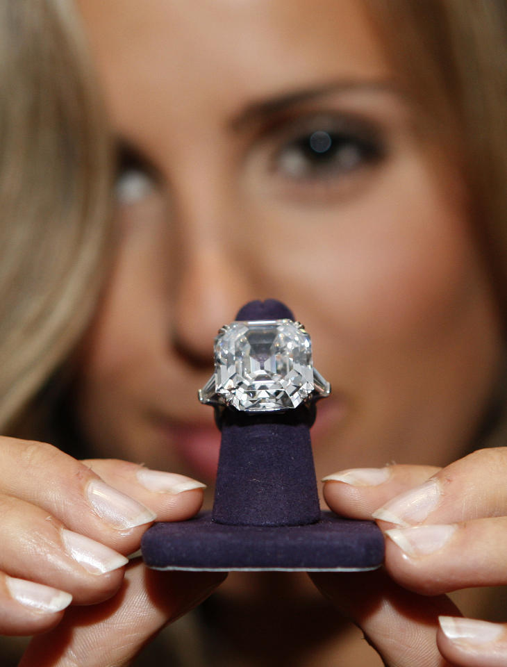 """FILE - In this Sept. 23, 2011 file photo, a woman displays """"The Elizabeth Taylor Diamond,"""" a 33.19 carat ring, which was a gift from Richard Burton, and worn by the actress during a press preview of Taylor's possessions at Christie's London. The piece is part of a collection available for viewing in New York on Saturday, Dec. 3. The collection will be up for auction in person and online, a first for Christie's, from Dec. 13-17. (AP Photo/Akira Suemori, file)"""