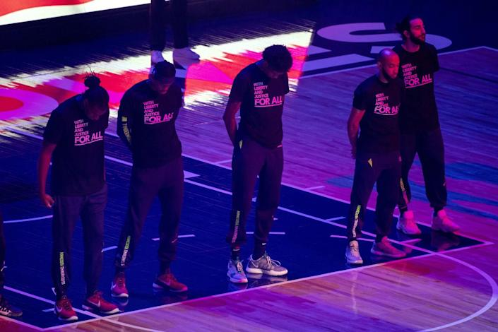 """The Minnesota Timberwolves, pictured, and the Brooklyn Nets wear T-shirts that read """"With liberty and justice for all"""""""