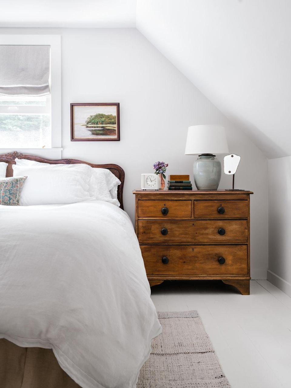 """<p>While we can't all live in a picture-perfect cottage in the mountains, we <em>can</em> channel those vibes through a mix of natural wood, soft linens, and delicate gray wall color. To bring a dose of similar peace and quiet into your own rest space, seek out an ethereal white-gray mix that will highlight the natural light of your room.</p><p><strong>Get the Look:</strong><br>Wall Paint Color: try <a href=""""https://www.benjaminmoore.com/en-us/color-overview/find-your-color/color/2124-70/distant-gray"""" rel=""""nofollow noopener"""" target=""""_blank"""" data-ylk=""""slk:Distant Gray by Benjamin Moore"""" class=""""link rapid-noclick-resp"""">Distant Gray by Benjamin Moore</a></p>"""