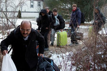A group that claimed to be from Turkey crosses the U.S.-Canada border illegally leading into Hemmingford, Quebec, Canada March 6, 2017.  REUTERS/Christinne Muschi