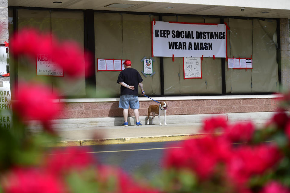"BELLMAWR, NJ - MAY 20: A man walking his dog reads notices outside of Atilis Gym below a placard stating ""KEEP SOCIAL DISTANCE WEAR A MASK"" on May 20, 2020 in Bellmawr, New Jersey. The gym has opened for the third consecutive day, defying the New Jersey Governor's mandate that many retail businesses stay closed due to the coronavirus pandemic.  (Photo by Mark Makela/Getty Images)"