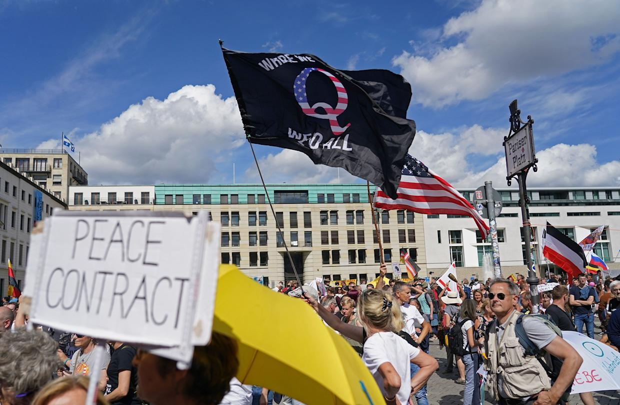 A man waves a QAnon conspiracy flag at a protest of coronavirus skeptics, right-wing extremists and others angry over coronavirus-related restrictions and government policy on August 29, in Berlin, Germany.