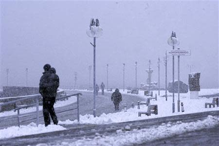 People walk during snowfall caused by hurricane-force Xaver in Gdynia