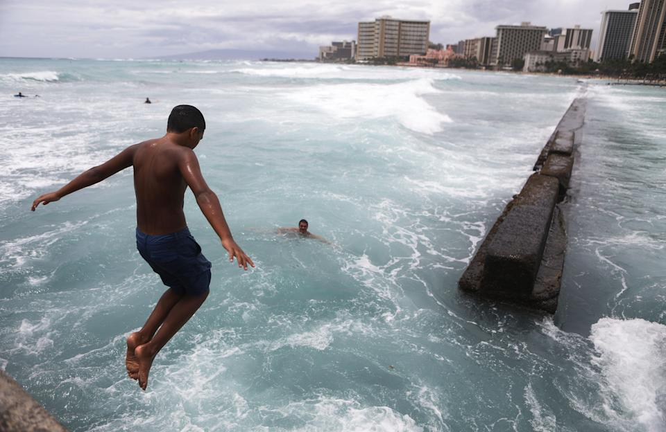 <p>A local resident dives into the water at Waikiki beach on Oahu island on Aug. 24, 2018 in Honolulu, Hawaii. (Photo: Mario Tama/Getty Images) </p>