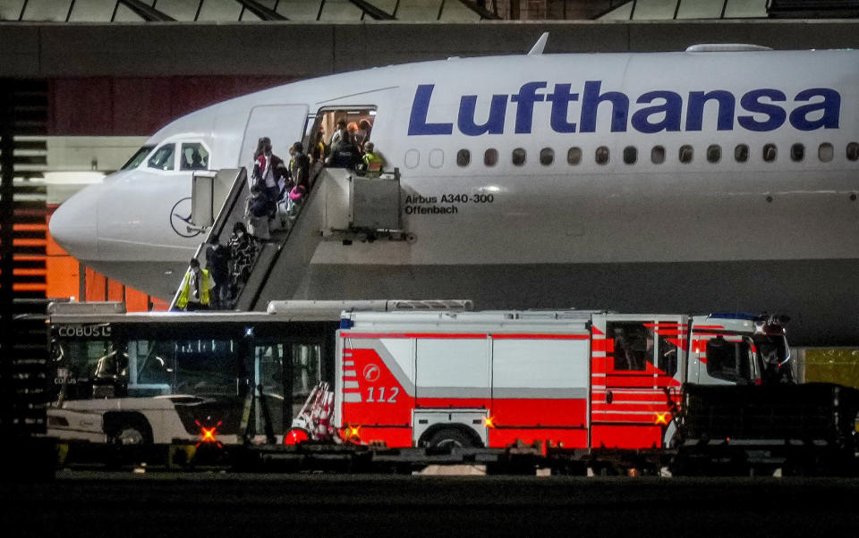 FILE - In this Aug. 18, 2021, file photo, people disembark from a Lufthansa aircraft coming from Tashkent in Uzbekistan that landed at the airport in Frankfurt, Germany. On board were about 130 people that were evacuated from Afghanistan. (AP Photo/Michael Probst, File)