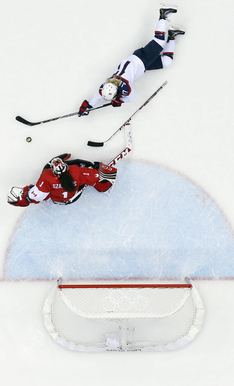 Goalkeeper Shannon Szabados of Canada (1) blocks a shot by Jocelyne Lamoureux of the United States (17) during the women's gold medal ice hockey game at the 2014 Winter Olympics, Thursday, Feb. 20, 2014, in Sochi, Russia. (AP Photo/David J. Phillip )