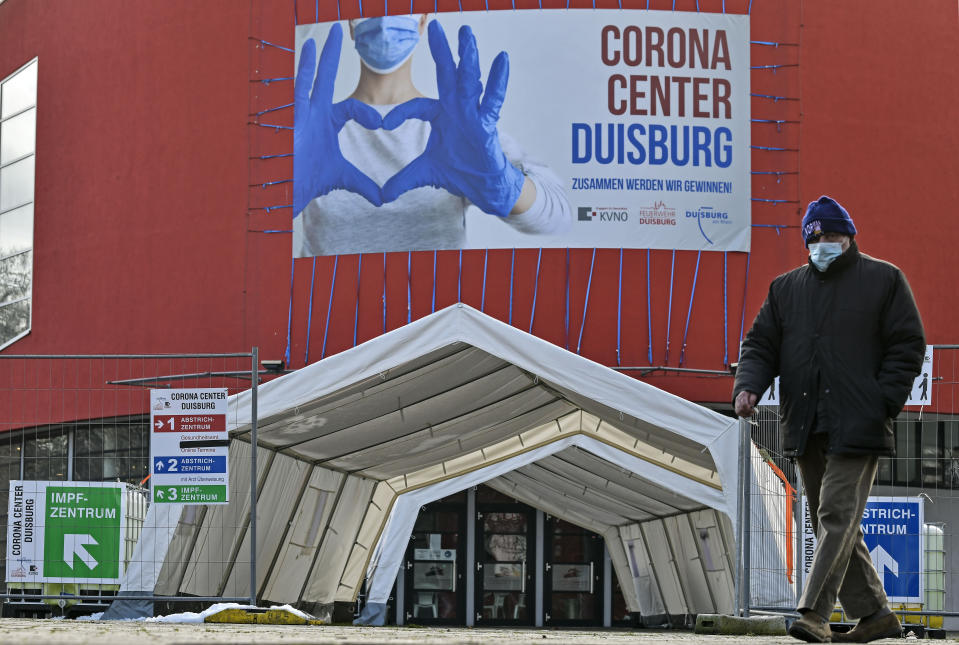 FILE - In this Monday, Jan. 25, 2021 file photo, a man wearing a face mask walks past the Corona Center in Duisburg, Germany. The former Musical theater has been turned into a COVID-19 test and vaccination center. With accusations of being slow off the blocks in the race to immunise its citizens against COVID-19, Germany faces the problem of having a glut of vaccines and not enough arms to inject. With its national vaccine campaign lagging far behind that of Israel, Britain and the United States, there are growing calls in this country of 83 million to ditch or rewrite the rulebook. (AP Photo/Martin Meissner, File)