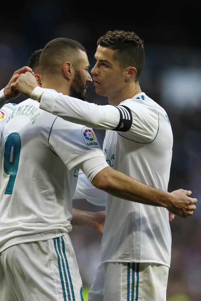 Real Madrid's Karim Benzema, left, celebrates with teammate Cristiano Ronaldo after scoring their side's fourth goal against Alaves during the Spanish La Liga soccer match between Real Madrid and Alaves at the Santiago Bernabeu stadium in Madrid, Saturday, Feb. 24, 2018. Ronaldo scored twice and Benzema once in Real Madrid's 4-0 victory. (AP Photo/Francisco Seco)
