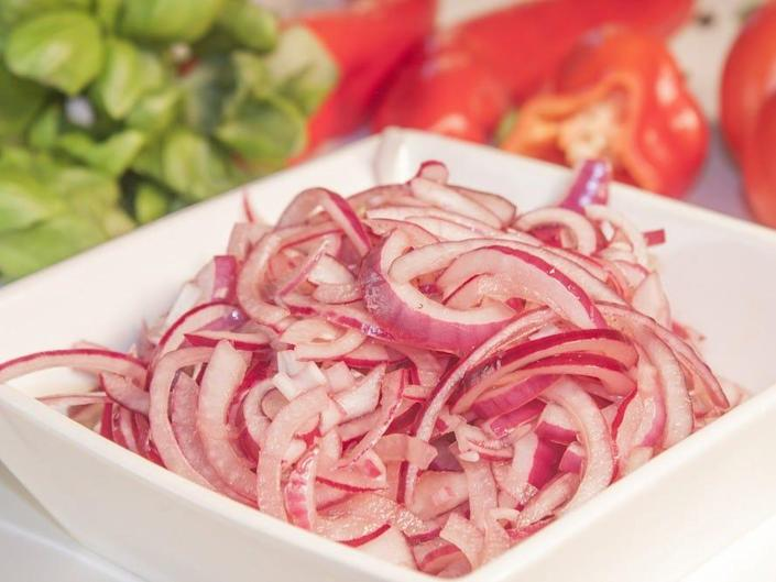 pickled red onion in a white bowl