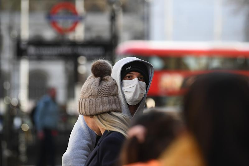 A man at a bust stop in Whitehall, London, wearing a protective facemask on the day that Health Secretary Matt Hancock said that the number of people diagnosed with coronavirus in the UK has risen to 51.