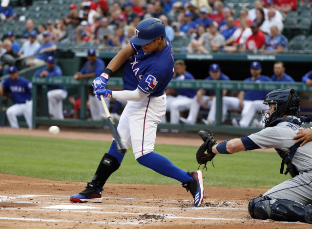 Texas Rangers' Shin-Soo Choo, left, connects for a single that he stretched into a double in the first inning of a baseball game as Seattle Mariners' Tom Murphy looks on in Arlington, Texas, Monday, May 20, 2019. (AP Photo/Tony Gutierrez)