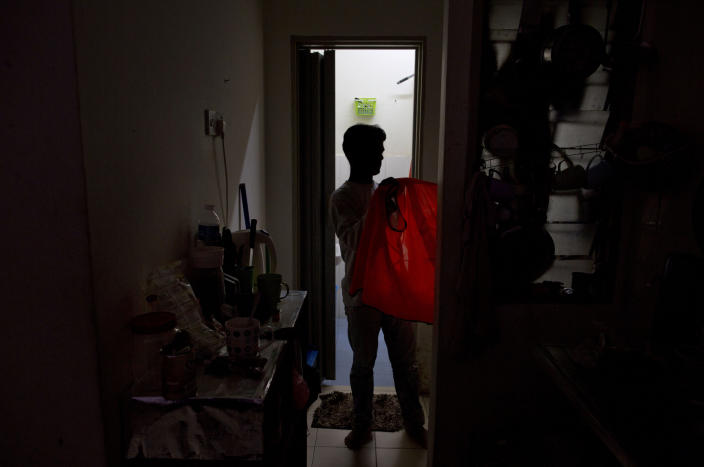 Shamshu, a member of Myanmar's long-persecuted Rohingya minority, changes clothes upon returning home in peninsular Malaysia, Monday, March 4, 2019. Shamshu is part of an invisible workforce made up of millions of poor laborers, including many who face exploitation and abuse, within Malaysia and neighboring Indonesia. Together, the two countries produce an estimated 85 percent of the world's $65 billion palm oil supply. (AP Photo/Gemunu Amarasinghe)