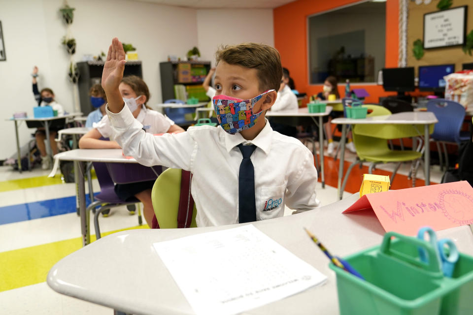 FILE - In this Monday, Aug. 23, 2021, file photo, student Winston Wallace, 9, raises his hand in class at iPrep Academy on the first day of school in Miami. A judge has ruled that Florida school districts may impose mask mandates. Leon County Circuit Judge John C. Cooper on Friday agreed with a group of parents who claimed in a lawsuit that Gov. Ron DeSantis' ban on the mandates is unconstitutional and cannot be enforced. (AP Photo/Lynne Sladky, File)