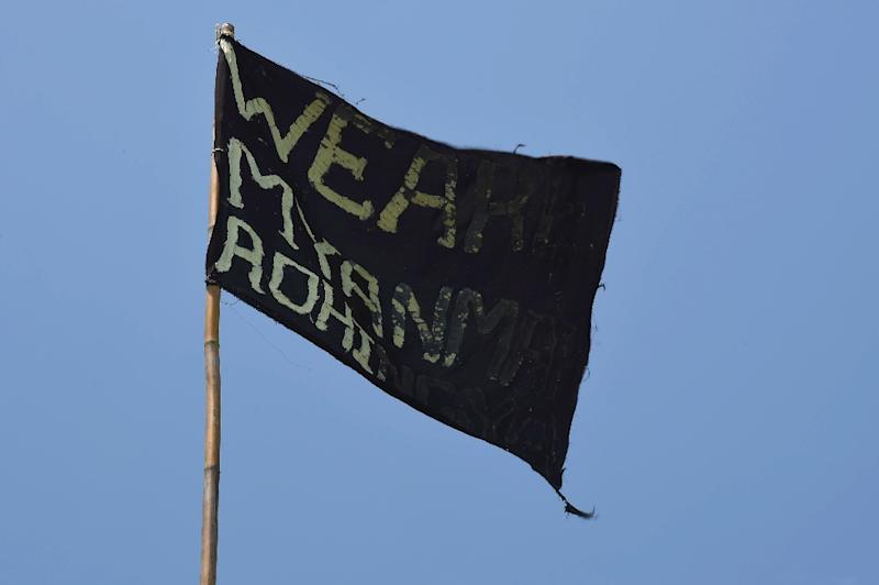 """A black flag with the words """"We Are Myanmar Rohingya"""" flies on a bamboo pole on an abandoned boat that carried Rohingya migrants who were rescued earlier in the day, off the coast near the city of Geulumpang in Indonesia on May 20, 2015 (AFP Photo/Romeo Gacad)"""