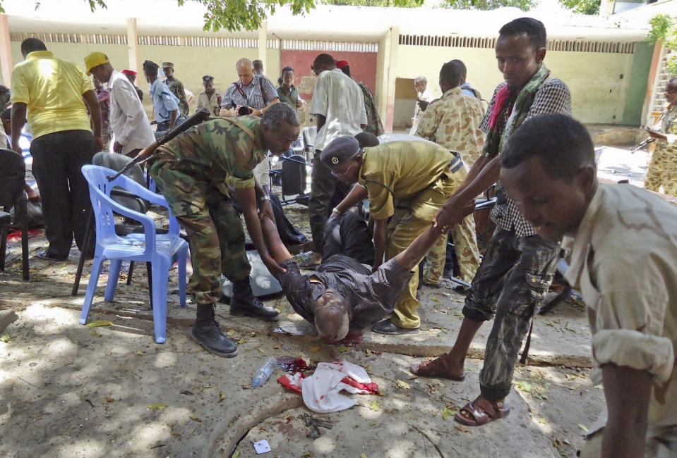 Somalis help a man wounded in a blast at the Somali National Theater in Mogadishu, Somalia Wednesday, April 4, 2012. A suicide blast during a ceremony at Somalia's newly reopened national theater on Wednesday killed at least 10 people, including two of the country's top sports officials, officials said (AP Photo/Farah Abdi Warsameh)