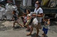 Celia da Costa Gomes, resident of Paraisopolis favela, walks home with her children after receiving a meal, in Sao Paulo, Brazil, on January 28, 2021