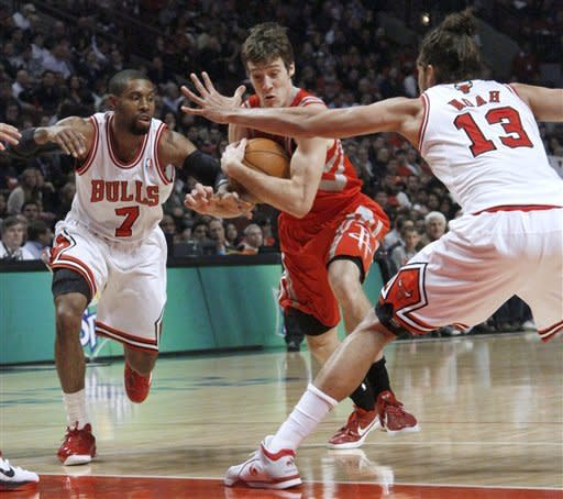 Houston Rockets guard Goran Dragic drives between Chicago Bulls guard C.J. Watson (7) and center Joakim Noah during the first half of an NBA basketball game Monday, April 2, 2012, in Chicago. (AP Photo/Charles Rex Arbogast)